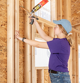 Woman applying sealant a construction site