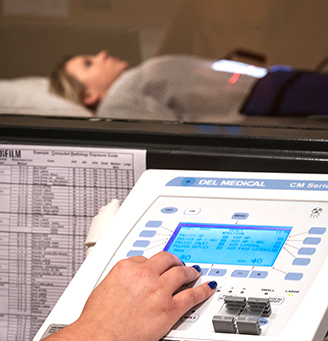 Radiology tech's hand on a control with paitent in the background